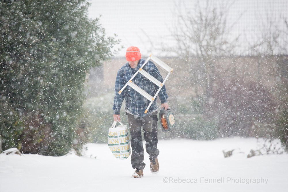 Man walking in snow with lots of bags and ldder